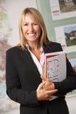 Retrato del agente de la propiedad inmobiliaria de sexo femenino en oficina Fotos de archivo libres de regalías