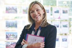 Retrato del agente de la propiedad inmobiliaria de sexo femenino en oficina Fotografía de archivo libre de regalías