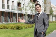 Retrato del agente inmobiliario confiado que presenta el edificio de oficinas imagen de archivo