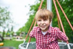 Retrato del aire libre del muchacho preescolar lindo en el patio en fondo verde natural fotos de archivo