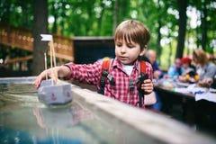 Retrato del aire libre del muchacho preescolar lindo que juega la nave hecha en casa en el parque fotografía de archivo