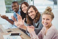 Retrato del alto ángulo de los hombres de negocios sonrientes que aplauden en el escritorio fotos de archivo