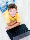 Retrato del alto ángulo del muchacho con la computadora portátil fotos de archivo