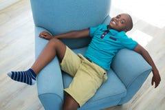 Retrato del alto ángulo del muchacho que miente en la butaca en casa imagenes de archivo