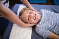 Retrato del alto ángulo del muchacho sonriente sonriente que recibe masaje de terapeuta de sexo femenino foto de archivo libre de regalías