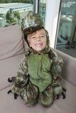 Retrato del alto ángulo del muchacho feliz en el traje del dinosaurio que se sienta en el sofá en casa Foto de archivo