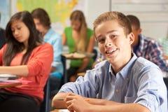 Retrato del alumno masculino que estudia en el escritorio en sala de clase Fotografía de archivo libre de regalías