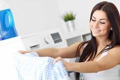 Retrato del ama de casa joven con el lavadero al lado de la lavadora Fotografía de archivo