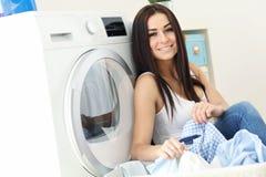 Retrato del ama de casa joven con el lavadero al lado de la lavadora Fotos de archivo libres de regalías