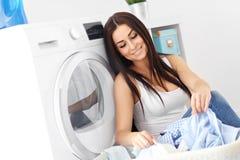 Retrato del ama de casa joven con el lavadero al lado de la lavadora Fotos de archivo