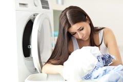Retrato del ama de casa joven con el lavadero al lado de la lavadora Fotografía de archivo libre de regalías