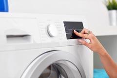Retrato del ama de casa joven con el lavadero al lado de la lavadora Imagenes de archivo