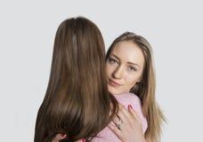 Retrato del amigo de abarcamiento de la muchacha contra el fondo blanco Imagen de archivo libre de regalías