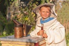 Retrato del apicultor de un muchacho joven que trabaja en el colmenar en la colmena con el fumador para las abejas Imagenes de archivo
