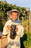 Retrato del apicultor de un muchacho joven que trabaja en el colmenar en la colmena con el fumador para las abejas a disposición Imágenes de archivo libres de regalías