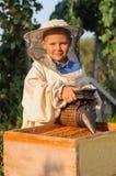 Retrato del apicultor de un muchacho joven que trabaja en el colmenar en la colmena con el fumador para las abejas a disposición Fotos de archivo libres de regalías