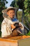 Retrato del apicultor de un muchacho joven que trabaja en el colmenar en la colmena con el fumador para las abejas a disposición Fotografía de archivo