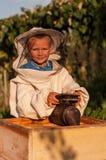 Retrato del apicultor de un muchacho joven que trabaja en el colmenar en la colmena con el fumador para las abejas a disposición Fotografía de archivo libre de regalías