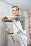 Retrato del aprendiz joven del pintor que pone el papel pintado fotografía de archivo libre de regalías