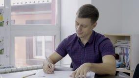 Retrato del arquitecto de sexo masculino joven, que está trabajando en oficina de la ensenada metrajes