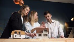 Retrato del arquitecto joven tres durante día del trabajo en la oficina metrajes