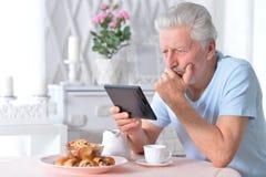 Retrato del artículo de la lectura del hombre mayor de la tableta imágenes de archivo libres de regalías
