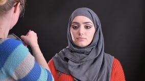 Retrato del artista de maquillaje en los vidrios que ponen en el highlighter con el cepillo plano en cara de la mujer musulmán at almacen de metraje de vídeo