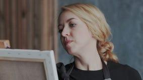Retrato del artista enfocado concentrado que trabaja con las herramientas especiales Ella que usa el paleta-cuchillo y el shpatul almacen de metraje de vídeo