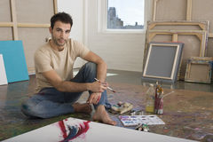 Retrato del artista With Painting Tools en estudio Imagenes de archivo