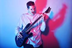Retrato del artista que canta, griterío del hombre joven, jugando la afición de la guitarra eléctrica, concepto de la música Estr Imagen de archivo libre de regalías