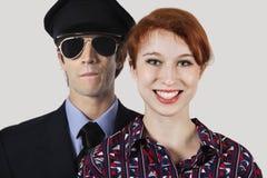 Retrato del asistente y del piloto de sexo femenino felices de vuelo contra fondo gris Imagen de archivo libre de regalías