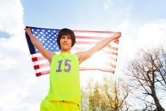 Retrato del atleta adolescente que sostiene la bandera americana Imagenes de archivo