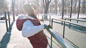 Retrato del atleta de la muchacha en un sombrero con los guantes y un chaleco caliente que hace ejercicios en barras desiguales e metrajes
