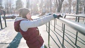 Retrato del atleta de la muchacha en un sombrero con los guantes y un chaleco caliente que hace ejercicios en barras desiguales e almacen de metraje de vídeo