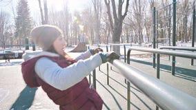 Retrato del atleta de la muchacha en un sombrero con los guantes y un chaleco caliente que hace ejercicios en barras desiguales e almacen de video