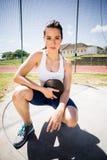 Retrato del atleta de sexo femenino confiado que lleva a cabo un disco Foto de archivo libre de regalías