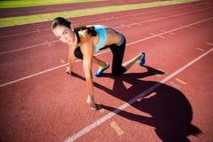 Retrato del atleta de sexo femenino en listo a la posición de funcionamiento Foto de archivo libre de regalías