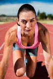 Retrato del atleta de sexo femenino en listo a la posición de funcionamiento Fotos de archivo libres de regalías