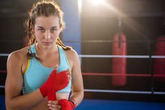 Retrato del atleta de sexo femenino joven que envuelve el vendaje rojo a mano foto de archivo