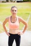 Retrato del atleta de sexo femenino que se coloca con las manos en caderas Imagen de archivo libre de regalías