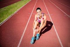 Retrato del atleta de sexo femenino que se sienta en pista corriente Imagenes de archivo