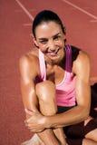 Retrato del atleta de sexo femenino que se sienta en pista corriente Foto de archivo