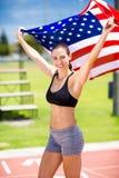 Retrato del atleta de sexo femenino que soporta la bandera americana en pista corriente Foto de archivo libre de regalías