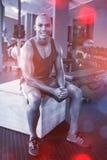 Retrato del atleta de sexo masculino que se sienta en la caja de madera Imagen de archivo libre de regalías