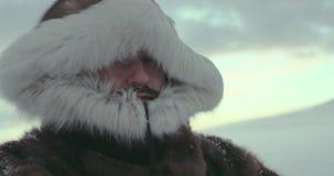 Retrato del aventurero en chaqueta tradicional del reno con la capilla de la piel Es nevoso y ventoso Tirado en cine ROJO almacen de video
