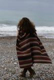 retrato del backview de la mujer morena feliz en el poncho que lleva de la playa fotos de archivo