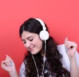 Retrato del baile adolescente feliz de la muchacha y de la música que escucha contra Imagen de archivo