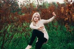Retrato del baile asustado de la chica joven entre los árboles muertos Fotos de archivo libres de regalías
