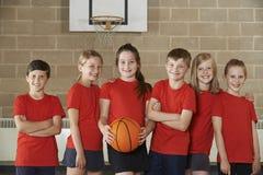Retrato del baloncesto Team In Gym de la escuela imagen de archivo