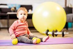 Retrato del bebé con pesas de gimnasia y la bola de la aptitud en casa fotos de archivo libres de regalías